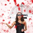 Pretty woman under umbrella with petals around her — Stock Photo