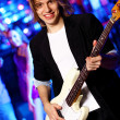 Young guitar player performing in night club — Стоковая фотография