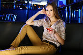Attractive woman in night club with a drink — Foto Stock