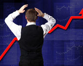 Young businessman against financial graphs — Stock Photo