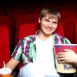 Young man in cinema watching movie - Stock fotografie