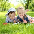 Children in the park reading a book — Stock Photo #9916435