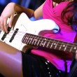 Young guitar player performing in night club - Stock Photo