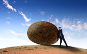 Businessman rolling a giant stone — Stock Photo