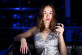 Young woman in night club with a drink — Foto de Stock