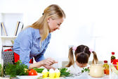 Young mother cooking at home with her daoghter — Stock Photo