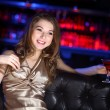 Young woman in night club with a drink — Stock Photo #9937295