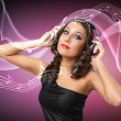 Young woman in evening dress with headphones - Stock fotografie