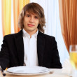 Young handsome msitting in restaurant — Stock Photo #9965646