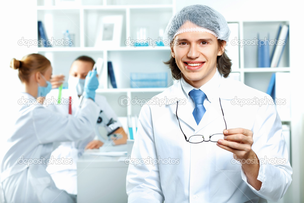 Young scientists in white uniform working in laboratory — Stock Photo #9965368