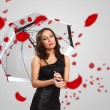 Pretty woman under umbrella with petals around her — Stock Photo #9984140