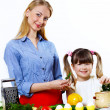 Young mother cooking at home with her daoghter - Stock Photo