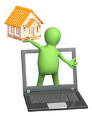 Puppet with laptop and house — Stock Photo