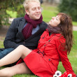 Stock Photo: Happy couple in love having a date and sitting on the grass
