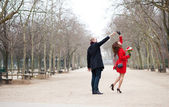 Happy couple dancing in the Luxembourg garden of Paris — Stock Photo
