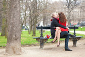Happy romantic couple hugging and kissing on a bench — Stock Photo