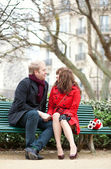 Dating couple sitting on a bench in Paris near the Notre Dame de — Stock Photo