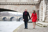 Beautiful romantic couple on a Parisian embankment at spring or — Stock Photo