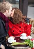 Happy couple kissing in Parisian cafe — Stock Photo