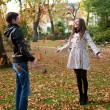 Happy young couple playing with leaves at fall — Stock Photo