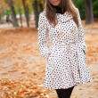 Beautiful young woman in polka dot trench at fall — Foto de Stock