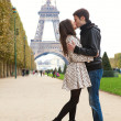 Young romantic couple kissing near the Eiffel Tower in Paris — Stock fotografie