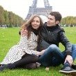 Young romantic couple sitting near the Eiffel tower — Stock Photo