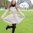 Beautiful young woman in polka dot trench near the Eiffel Tower - Stock Photo