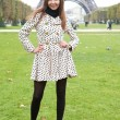 Beautiful young woman in polka dot trench near the Eiffel Tower — Stock Photo