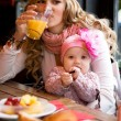 Young mother and baby daughter having breakfast together in a Pa — Stock Photo #9407386