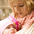 Stock Photo: Beautiful young mother carrying her baby daughter in sling