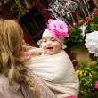Young mother with beautiful baby daughter in a garden. Mother is — Stock Photo #9407645
