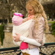Beautiful young mother with her baby daughter in sling — Stock Photo