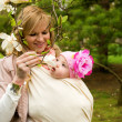 Beautiful young mother with her baby daughter in a garden at spr — Stock Photo #9407759