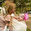 Stock Photo: Beautiful young mother with her baby daughter in a garden at spr