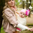 Beautiful young mother with her baby daughter in a garden at spr — Stock Photo #9407782