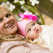 Beautiful young mother with her baby daughter in a garden at spr — Stock Photo