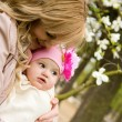 Beautiful young mother with her baby daughter in a garden — Stock Photo