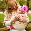 Beautiful young mother and baby daughter having fun outdoors at — Stock Photo