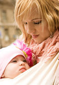 Beautiful young mother carrying her baby daughter in sling — Stock Photo