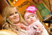 Beautiful young mother with baby daughter taking a ride on tradi — Stock Photo