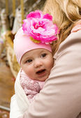 Cheerful beautiful baby girl in her mother's arms — Stock Photo