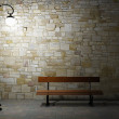 Illuminated brick wall with old fashioned street light and bench — Stock Photo