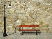 Brick wall with street light and bench — Stock Photo