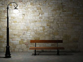 Illuminated brick wall with old fashioned street light and bench — Stok fotoğraf