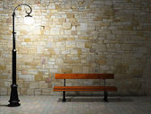 Illuminated brick wall with old street light and bench — Stock Photo
