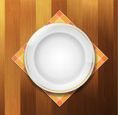 Plate with napkin on wood background — Vecteur