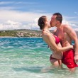 Handsome couple kissing in sea — Stock Photo