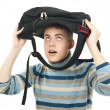 Stock Photo: Young happy male student with backpack on his head