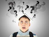 Stressed student with question marks over his head — Stock Photo